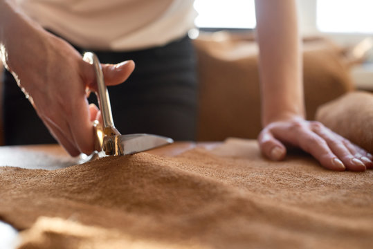 Female artisan cutting brown leather with scissors close up