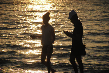 silhouett couple useing the smart phone on the beach in sunset time and reflex in ocean