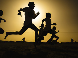 Silhouette of children running in field
