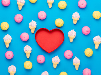 photo of tasty colorful marshmallows and heart shaped box on the wonderful blue background