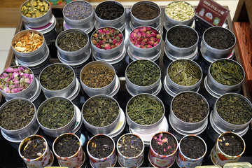 Various types of tea in metal pots exposed for sale in a Chinese tea shop in Shanghai