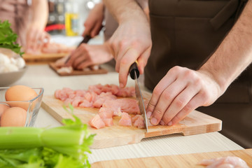 Man cutting chicken fillet at cooking classes