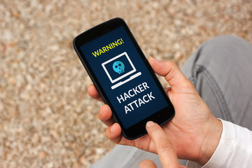 Hands holding smart phone with hacker attack concept on screen. All screen content is designed by me