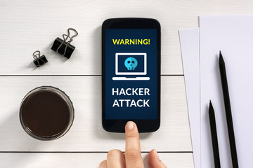 Hacker attack concept on smart phone screen with office objects on white wooden table. All screen content is designed by me. Flat lay