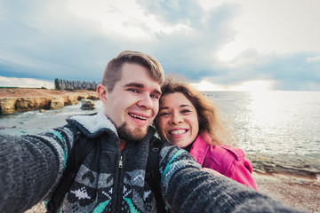 Young happy couple is taking selfie photo on vacation near sea.