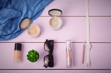 Sunglasses, cosmetics makeup and essentials on wooden background
