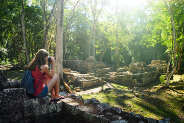 Woman traveller photographing ancient Mayan ruins.
