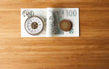 Time is money concept .Czech crowns on wooden background. Vintage watch.