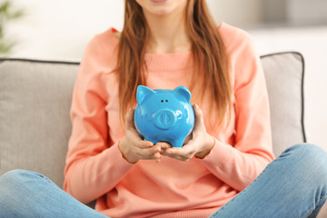 Beautiful young woman with piggy bank at home, closeup