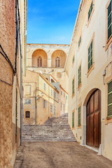 The narrow old street in the historic center of Arta, Mallorca, Spain. Beautiful sunny day for traveling and feel the atmosphere of the historic town.