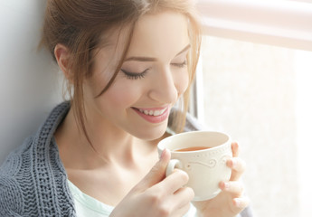 Beautiful young woman drinking tea near window at home
