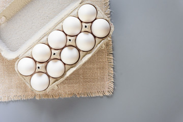 Cardboard egg rack with eggs on gray background. Top view.  Rural still life, natural organic healthy food.