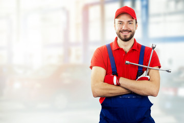 car repair service - smiling auto mechanic with wrench in hand