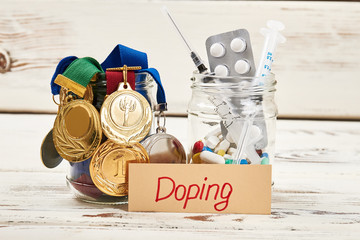 Medals, drugs and card. Load on health in sports.