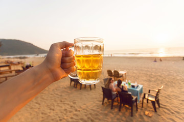 Glass of cold beer in hand of tourist at the beach with local cafe and some relaxing people.