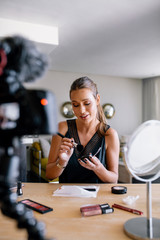Young female vlogger recording a make-up video for her vlog.