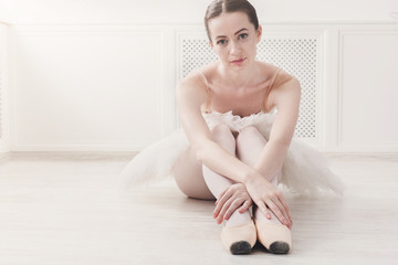 Closeup of young ballerina sit in pointe shoes on white floor background