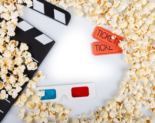 Black clapper movie, 3D-glasses, movie tickets and lot popcorn, isolated on white.