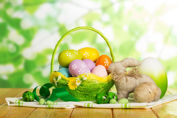 Colorful Easter eggs in basket, large egg, entwined in twine, bunny, candy.