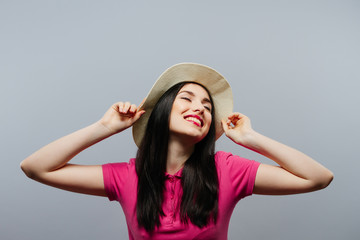Happy young woman posing over grey background.