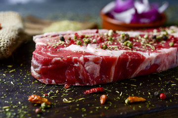 raw strip steak seasoned with different spices