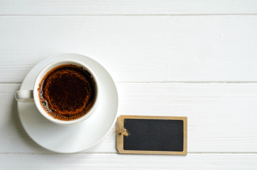 White cup of black coffee with a small black message board on white painted wooden background, copy space for your text