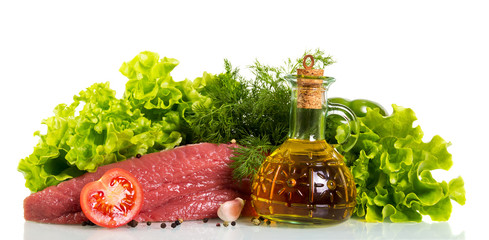 A piece of raw beef, bottle of butter, lettuce, part of tomato, dill, garlic and pepper is isolated on white.