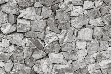 Closeup surface brick pattern at old stone brick wall textured background in black and white tone