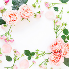 Round frame with pink roses on white background. Flat lay, top view. Floral background.
