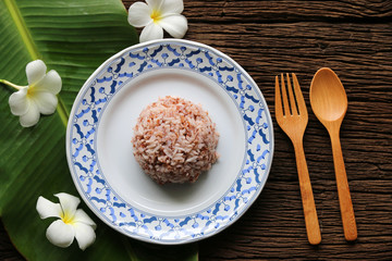 Cooked rice brown Jasmine From Thailand in ceramic dish on dark wood background