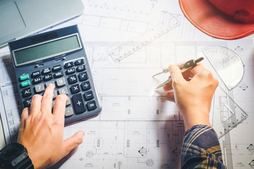 Architect or engineer working in office on blueprint. Architects workplace , blueprints, ruler, helmet and divider. Construction concept. Engineering tools
