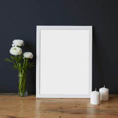 Empty white wooden picture frame on the table, art print mock-up, Scandinavian interior background. White poster canvas on grey wall with clean blank for design, advertising and other content picture