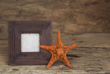 Vintage picture frame with star fish on wood table top background