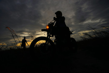 Silhouette of a man riding his motorcycle during sunset.