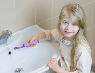 A little girl in the bathroom washes an electric toothbrush.