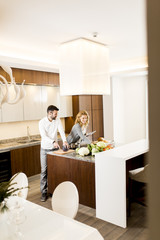 Pretty woman preparing vegetable salad with her husband near by