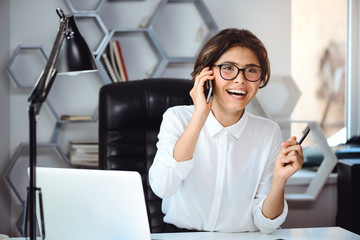 Young beautiful smiling businesswoman speaking on phone at workplace in office.