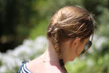 Belle femme de dos avec une tresse devant un décor de fleur et de nature
