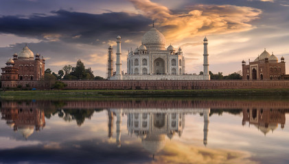 Wall Mural - Taj Mahal Agra at sunset as seen from the Yamuna river banks with a moody sky. Taj Mahal designated as a World Heritage Site is a masterpiece of Indian heritage and architecture.