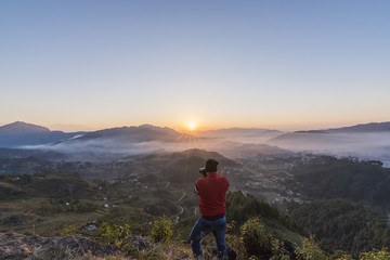 Photographer in action, clicking a beautiful Himalayan Sunrise.