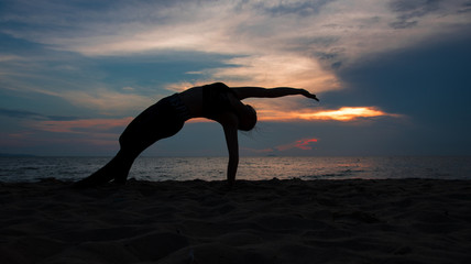 Silhouette of a woman playing yoga on twilight. Sunset sky background
