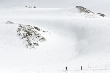 Skiers walking on snow covered mountain ranges