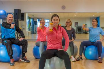 gruppe trainiert mit hanteln auf dem gymnastikball