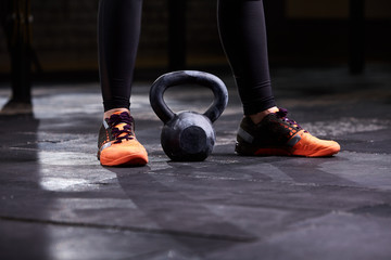 Cropped image of young woman, legs in the black leggings, orange sneakers and kettlebell. Crossfit workout