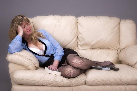 Woman sleeping on a cream leather sofa