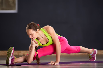 Woman practicing yoga in the splits position on the floor. In the gym.
