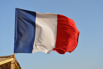 French flag waving in the wind against the blue sky