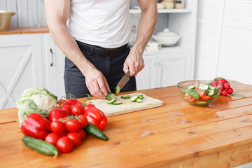 Middle-aged athlete, cuts vegetables salad of cucumber and tomato. Vegetarian food
