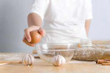 Close up shot hand of woman holding egg for braking shell with glass bowl to making bakery