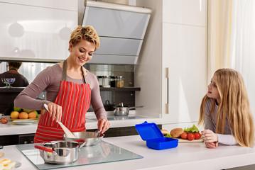 Joyful mother frying food on pan